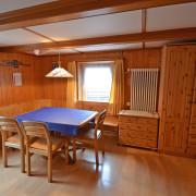 Wohnzimmer – Das gemütliche Wohnzimmer ist mit einem grossem Esstisch, zwei Klappsofas, Fernseher mit Satellitenempfang und Telefon ausgestattet. Auf Wunsch ist Internetzugang per LAN Anschluss verfügbar (1/3)