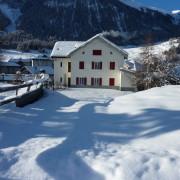 Jugendhaus Plazi Bergün – Grosse Terasse und Spielwiese hinter dem Haus (1/2)