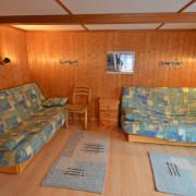 Wohnzimmer – Das gemütliche Wohnzimmer ist mit einem grossem Esstisch, zwei Klappsofas, Fernseher mit Satellitenempfang und Telefon ausgestattet. Auf Wunsch ist Internetzugang per LAN Anschluss verfügbar (3/3)
