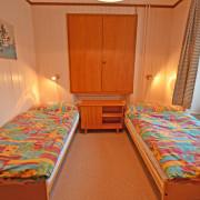 Schlafzimmer 2. Obergeschoss (Leiterzimmer) – Das Schlafzimmer auf dem Hauptstock umfasst 2 Betten mit Nachttischbeleuchtung, kleiner Tisch und Kleiderschrank.