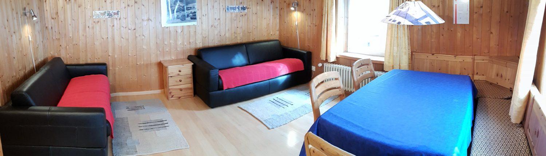 Wohnzimmer – Das gemütliche Wohnzimmer ist mit einem grossem Esstisch, zwei Klappsofas, Fernseher mit Satellitenempfang und Telefon ausgestattet. Auf Wunsch ist Internetzugang per LAN Anschluss verfügbar (2/3)