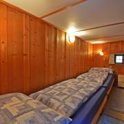 Schlafzimmer 2 – 2 Bett Schlafzimmer mit Kleiderkasten und Nachttischbeleuchtung.