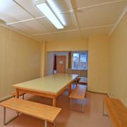 Aufenthaltsraum 1. Obergeschoss – Ausgerüstet mit 2 Tischen, Töggelikasten, Bänken und Sofa.